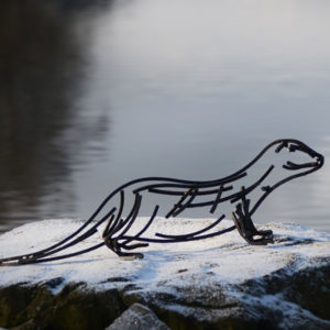 Watchful otter Wildlife Sculpture standing beside a river