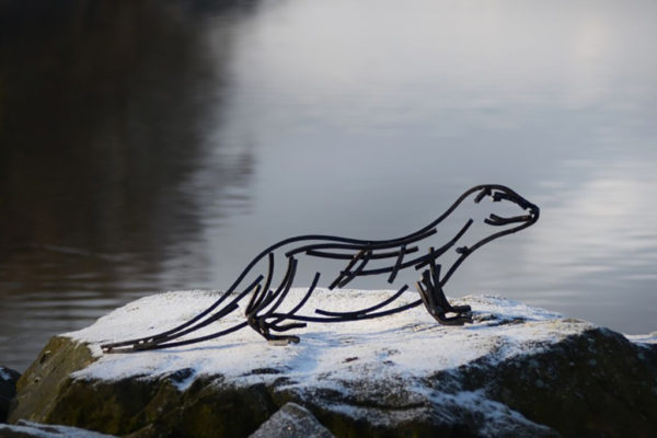 Watchful otter Wildlife Sculpture standing beside a river