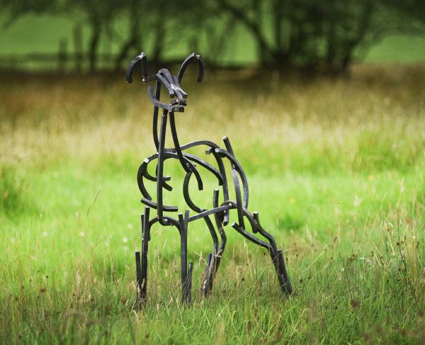 Young Fawn Wildlife Sculpture standing in the fields