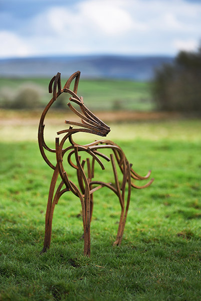 Dog Fox Wildlife Sculpture standing in the field in the winter sun