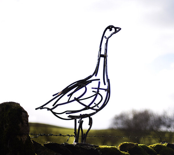 Snow Goose Wildlife Sculpture standing alert on a stone wall