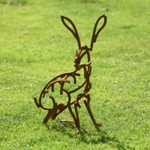 Small Hare Wildlife Sculpture sitting in the grass in the sunshine