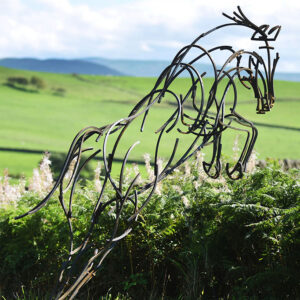 Hunter Wildlife Sculpture leaping over hedgerow in a summer chase